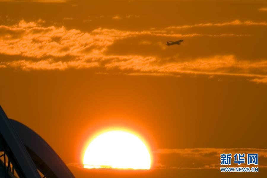 图为8月13日,一架民航飞机日出时在新加坡东岸